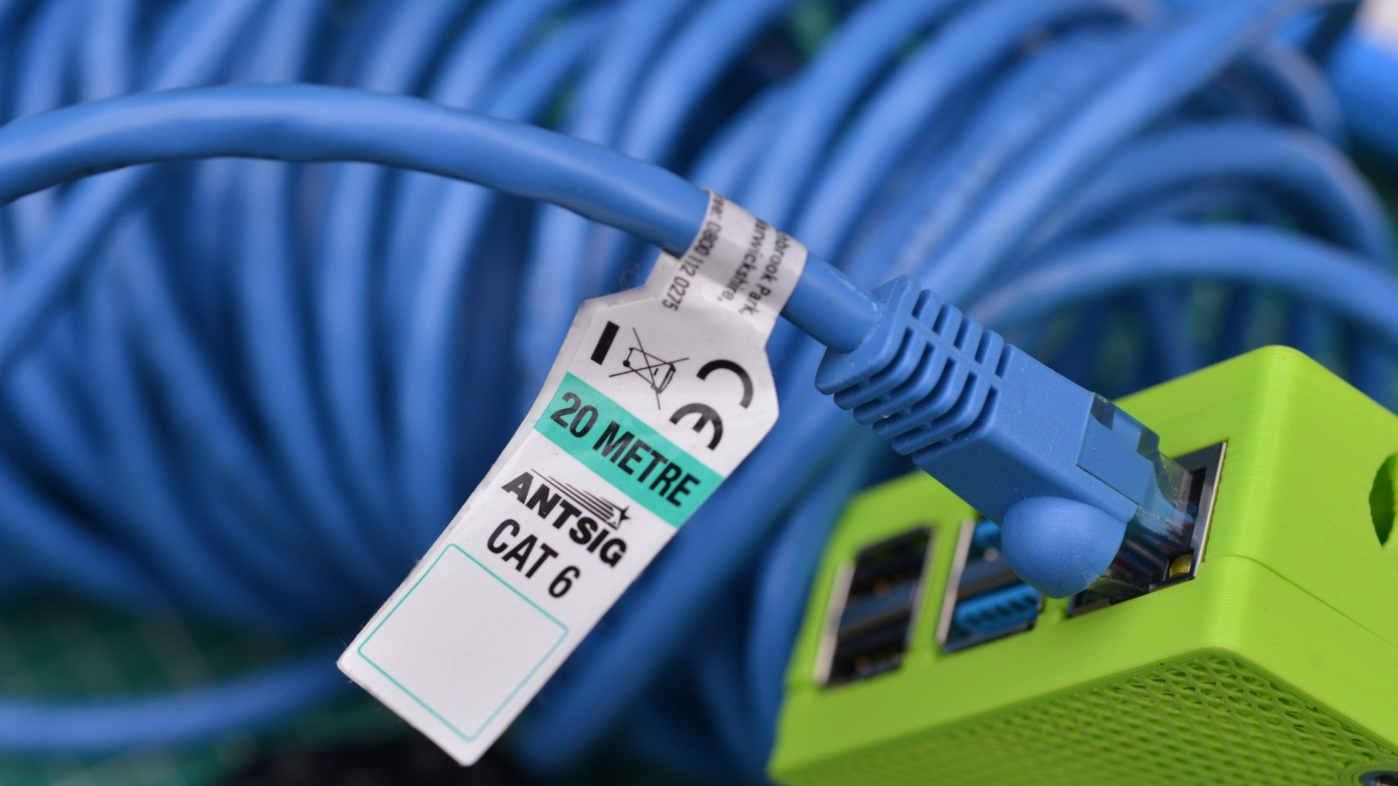 A bundle of blue CAT6 Ethernet cable plugged into a Raspberry Pi 4 housed in a bright green box.