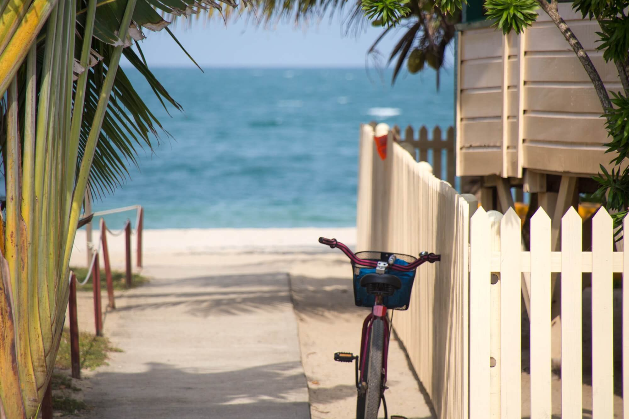Key West, Florida: A cute beach bicycle rests against a beach house fence, facing the sea and a sandy beach somewhere in the Florida Keys. This image first appeared on https://www.florida-guidebook.com/key-west/
